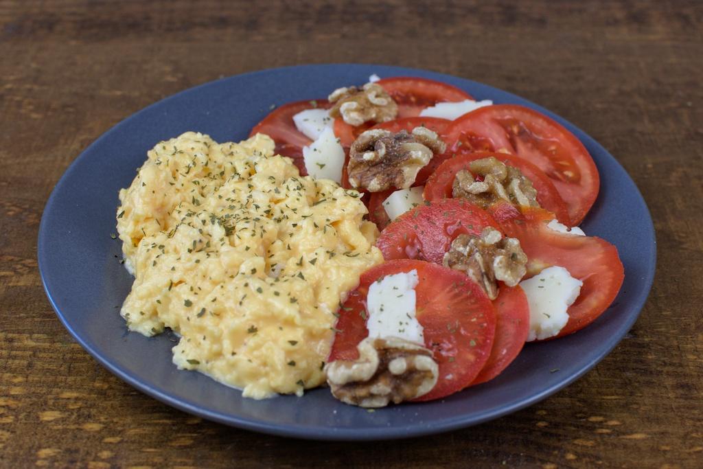 Huevos revueltos con ensalada de tomate, queso y nueces